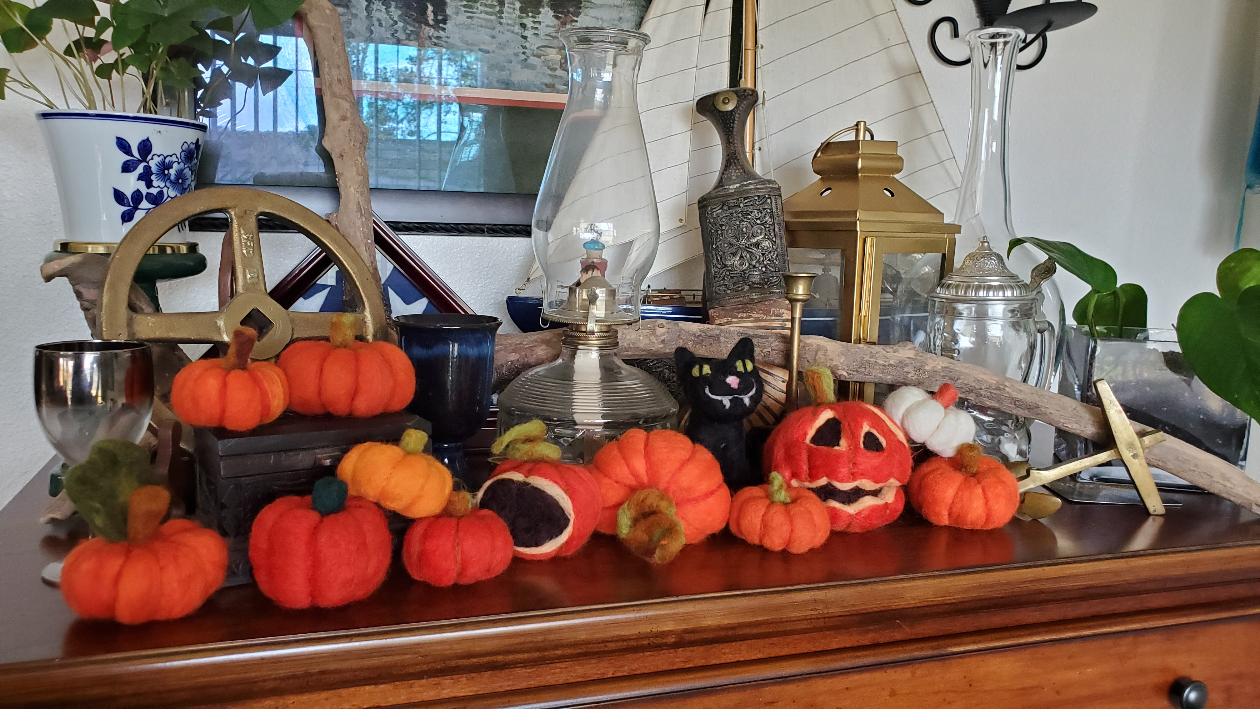 a wooden furniture top covered in small wool felted pumpkins