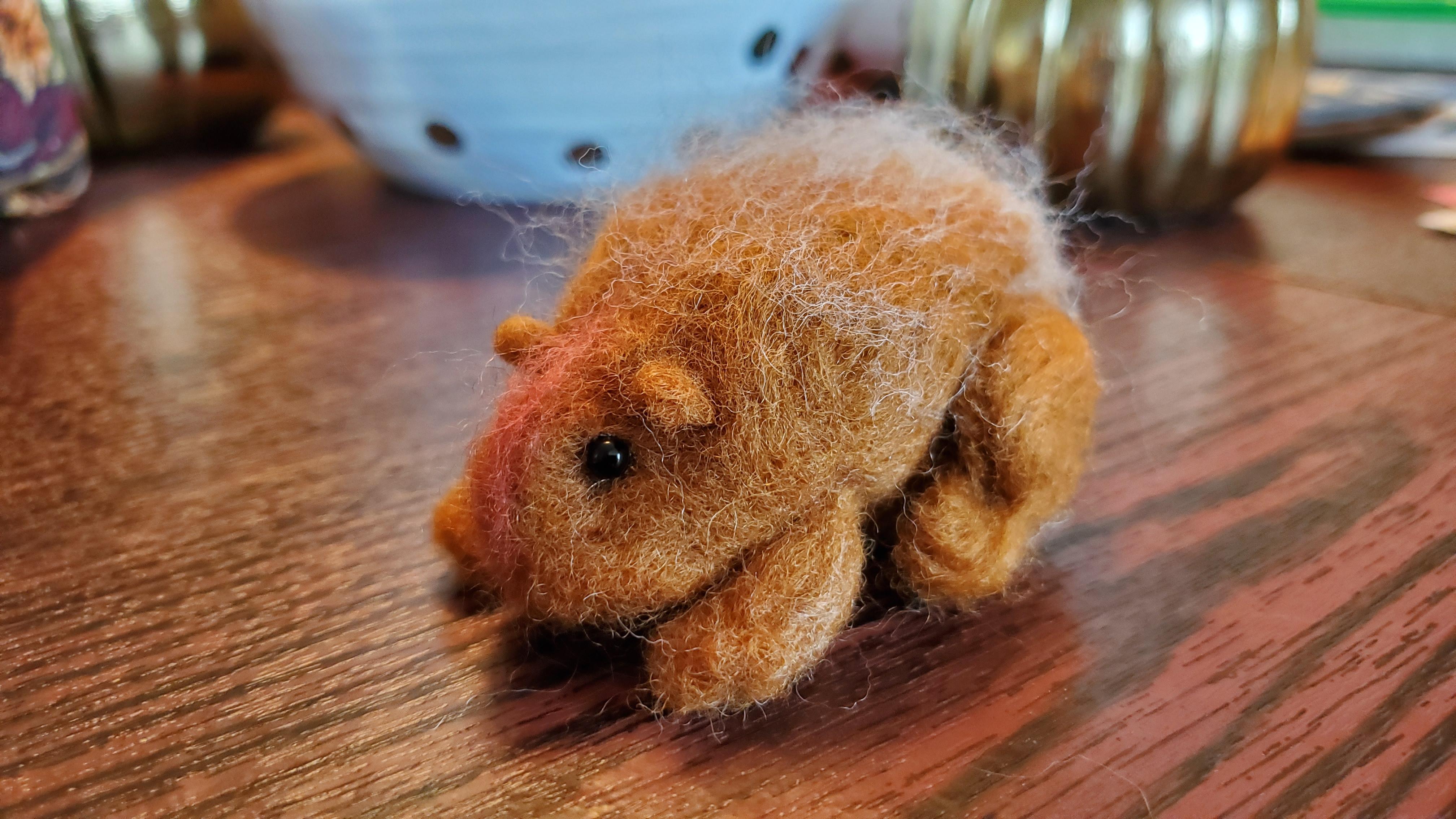 little felt porcupine with black bead eyes sitting on a table
