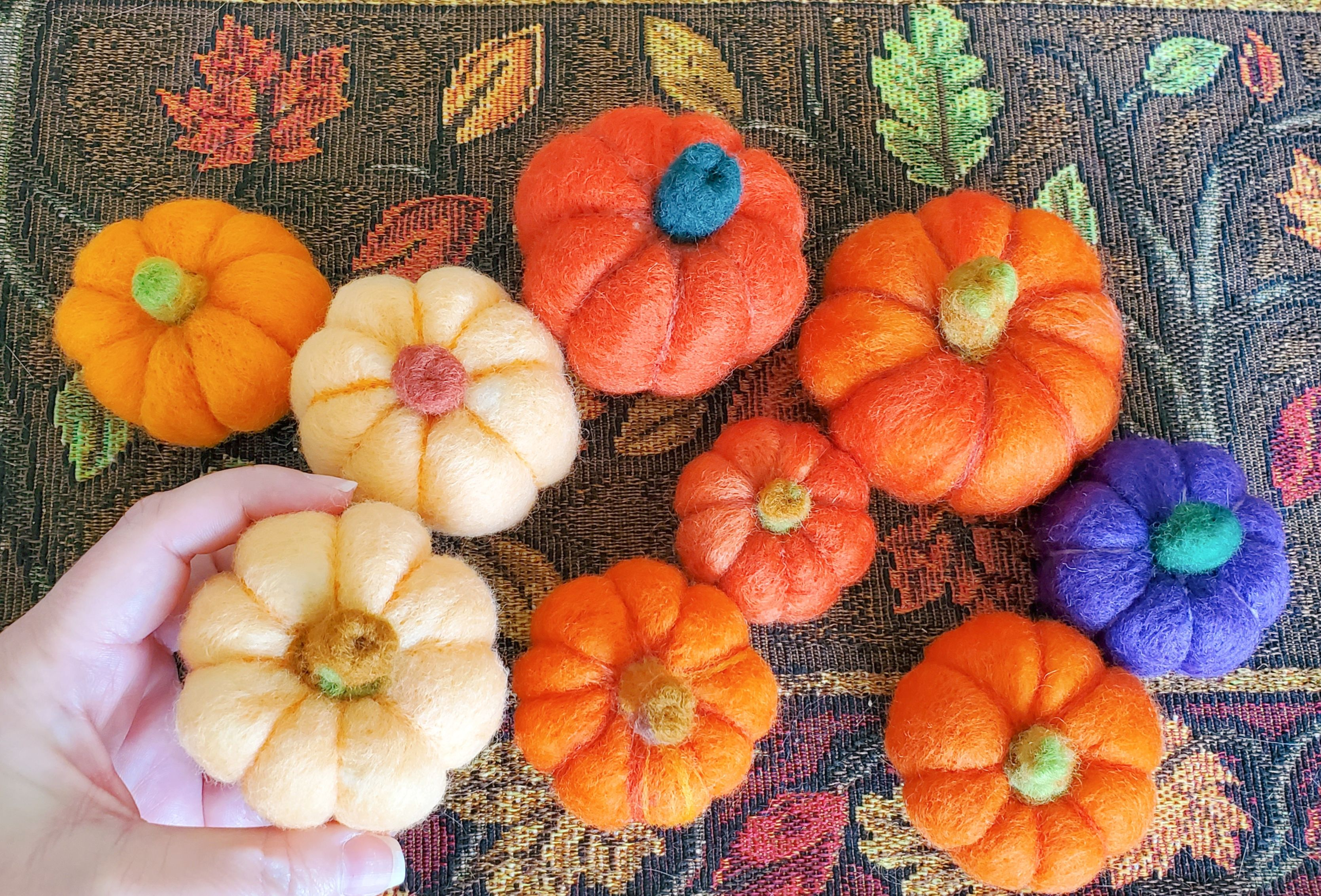 several small pumpkins with a hand holding one