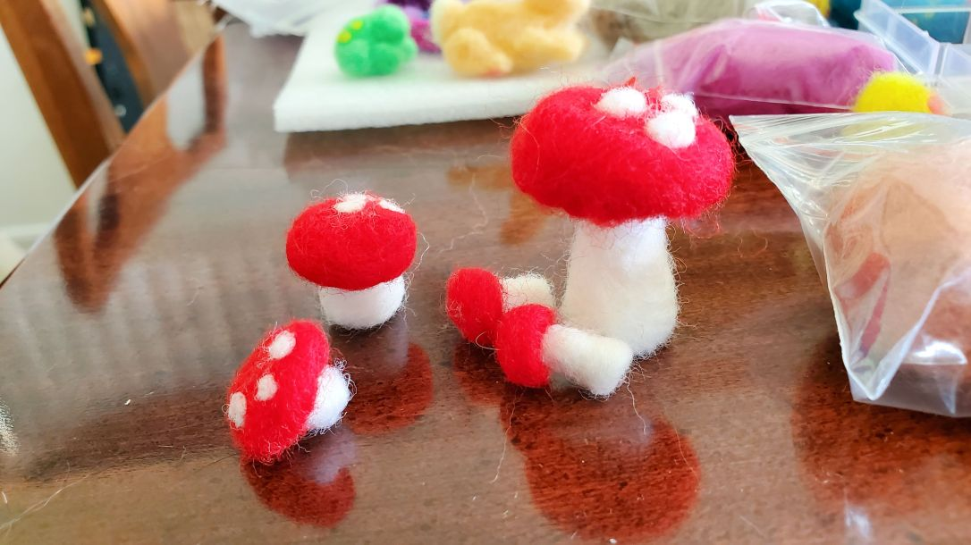 several small felt mushrooms, red with white spots on cap